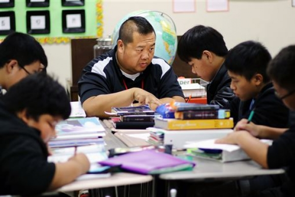 Bilingual education assistant Long Chang helps Hmong-speaking students with their schoolwork Thursday during Delong Midd