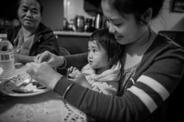 Leenee Vue helps her niece at the dinner table on November 2013 in Fresno, Calif. Two Hmong Americans are immigrants. By